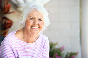 senior woman sitting outside of Independent Senior Living homes in florida